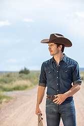 cowboy with dark hair and dark eyes with a lasso on a dirt road