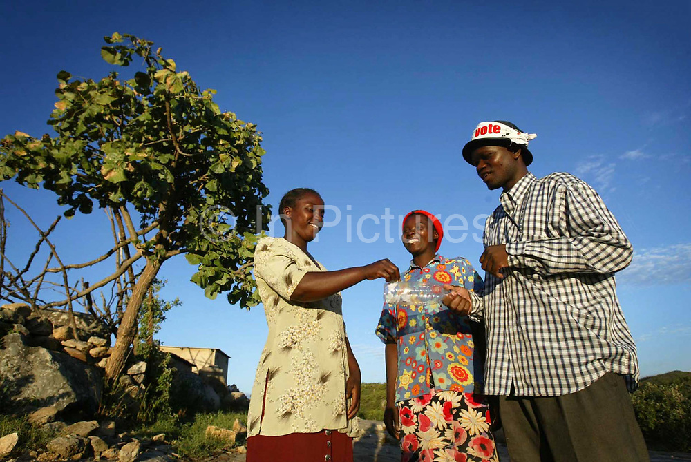 MDC Candidate for Makoni East constituency in Manicaland Piesha talks to constituents Cathrine Chabaya and Ronia Chiwandika during campaigning in his constituency during the Zimbabwe elections.