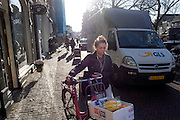 Een vrouw moet met haar fiets met boodschappen voorbij een vrachtwagen lopen die staat uit te laden op de Oudegracht in Utrecht.<br />
