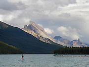 A stand-up paddleboarder makes his way across Maligne Lake on an overcast day. Jasper National Park, Jasper, Alberta, Canada.