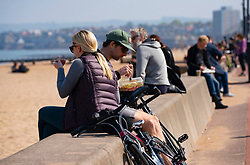 Portobello, Scotland, UK. 25 April 2020. Views of people outdoors on Saturday afternoon on the beach and promenade at Portobello, Edinburgh. Good weather has brought more people outdoors walking and cycling. Police are patrolling in vehicles but not stopping because most people seem to be observing social distancing. People sitting on seawall but maintaining social distancing.  Iain Masterton/Alamy Live News