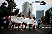 "TOKYO, JAPAN, 28 SEPTEMBER - Kasumigaseki - The woman's active group ""KNOW NEW KISS"" (Japanese phonetically : No Nukes) at the anti-nuclear demostration in front of  the National Diet Bulding (Kokkai Gijidou) - Following shyly the example of the Femen's Ukrainian activist, they use the charm of their  naked shoulder an belly to protest about  the resuption of the nuclear power after Fukushima's crisis. - September 2012"