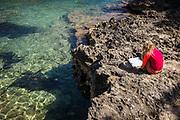 Calo de sa barca trencada, Mallorca, girl reading on the rocky beach