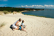 Mother, daughter and son play in the sand, Nida, Lithuania; MRs on file