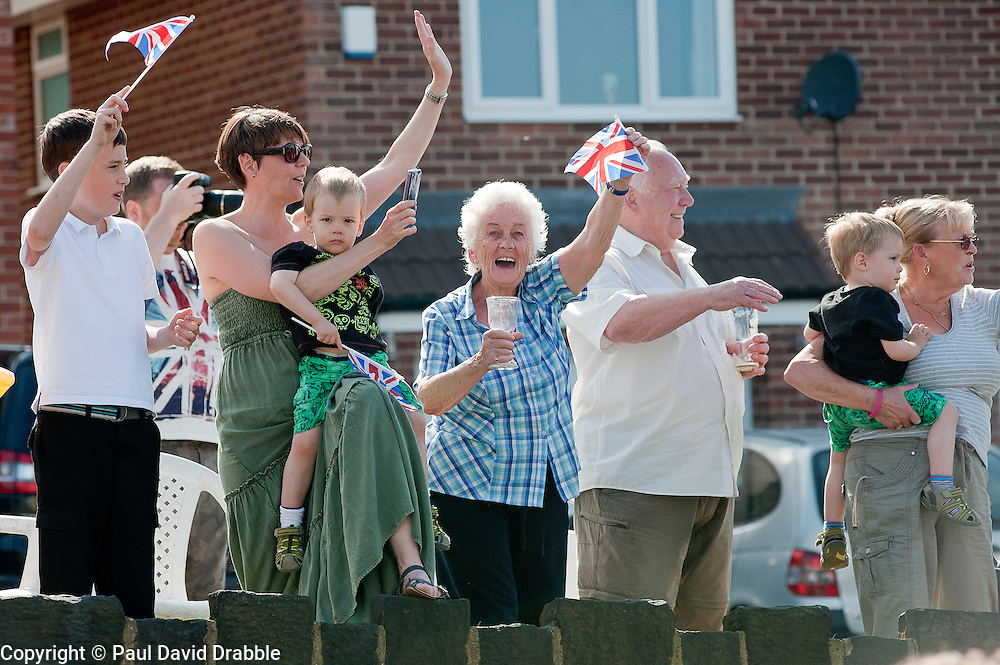 Olympic Torch reaches Sheffield Chapeltown/Ecclesfield/Parson Cross leg.<br /> Locals cheer on the torch bearer from a raised section of Ecclesfield Rd Close to Cowley View Road<br /> 25 June 2012.Image © Paul David Drabble