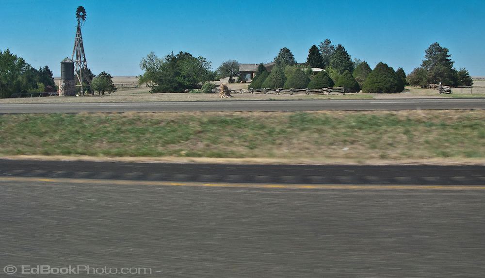 a lone farmhouse and windmill surrounded by windbreak coniferous trees in flat rural west Texas along interstate 20 panorama