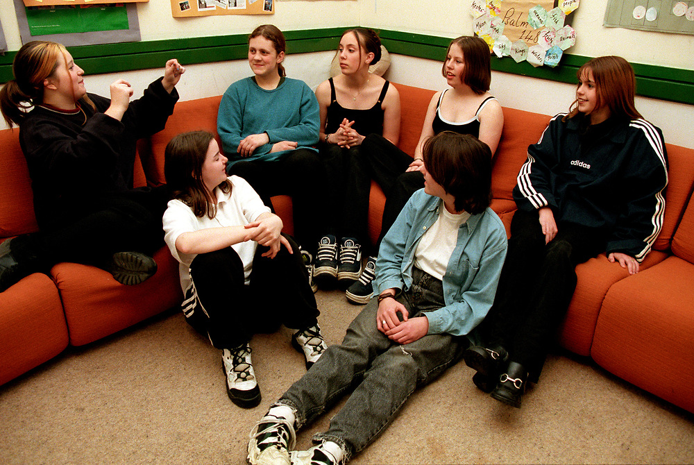 Group of teenage girls chatting at a youth club after school,