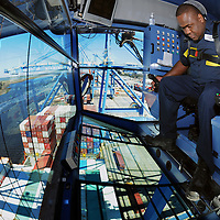 Tramel Johnson, a crane operator at the North Carolina State Port at Wilmington, moves cargo containers on to the Yang Ming Busan Thursday, March. 14, 2013. Photo by Michael Cline Photography