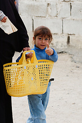 A Young Iraqi girl looks out from behind her mother and gives a thumbs up sign as a British Army patrol of Royal Dragoon Guards passes through Umm Qasr town Southern Iraq, while on Op-Telic in March 2005