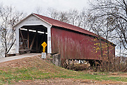 """McAllister Covered Bridge (126 feet long), built in 1914 by J.A. Britton over Little Raccoon Creek, on County Road 400S, Parke County, Indiana, USA. Red and white paint protects the wood. The """"Cross this bridge at a walk"""" sign requires slow vehicle speed."""