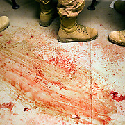 Canadian medics at a Canadian Forward Operating Base are seen standing on a blood stained floor while treating four Afghan civilians one of which later died from his wounds after they suffered injuries from an apparent improvised Explosive Device (IED) in Zhari District Afghanistan. Zhari and the adjacent Panjwai District have been the most volatile area of Afghanistan over the past two years and the site of NATO's largest ever land battle. Soldiers felt that the civilians injuries seemed more associated with an accident from setting an IED than stumbling across one.<br /> © Louie Palu/ZUMA Press/New America Foundation