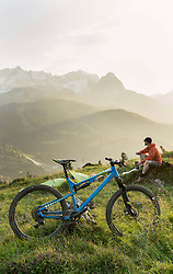 Mountain biker taking a break admiring scenic mountain view, Bavaria, Germany