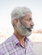 A man with a large beard, wearing a beard guard. Mehrangarh or Mehran Fort, one of the largest forts in India. Jodhpur is known as the Blue City.