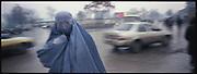 A woman in burqa walks on the rainy road in Kabul.