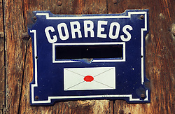 Blue enamel letterbox with the word Correos  post  printed on it along with a picture of an envelope,