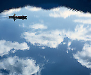 A lone canoeist paddles among reflected clouds on Emerald Lake, Yoho National Park, British Columbia Canada.