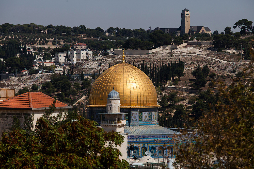 The Dome of the Rock Mosque with its golden cupola, located in the Al-Aqsa Mosque compound in the Old City of Jerusalem, is seen from the observation deck of the Hurva synagogue in the Jewish Quarter, backdropped by the Augusta Victoria Hospital located on top of the Mount of Olives.