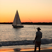 A man fishes while a sailboat passes by at sunset on Wrightsville Beach, NC.