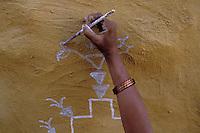 Inde - Rajasthan - Village des environs de Jaisalmer - Femme réalisant des peintures murales (Thapa)