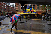 On a rainy day, pedestrians hurry past during a shower outside where the musical Singing in the Rain is playing. Prominently, a person carries a large brolley design with a Uniuon Jack flag and bright gree bag. To visitors, it is always raining in England, located on the eastern edge of the Atlantic. But April and May 2012 saw sustained above average ranfall while UK water companies still insisted on drought conditions throughout the country.