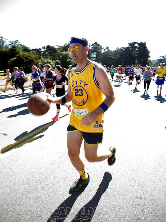 A man dressed as a member of the Golden State Warriors dribbles a basketball through Golden Gate park, during the 105th running of the Bay to Breakers 12k, Sunday, May 15, 2016 in San Francisco. The 7.42-mile race from San Francisco Bay to the Pacific Ocean, which attracts a field of tens of thousands of runners, from elite runners to weekend warriors, some clad in costume and some in nothing at all. (Photo by D. Ross Cameron)