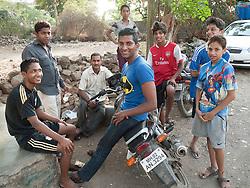 Group of men and boys round motorbike, Mumbai