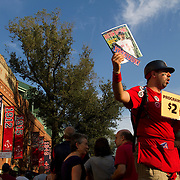 A Red Sox game program vendor shouts for sales outside the Fenway Park entrance before a summer evening game.