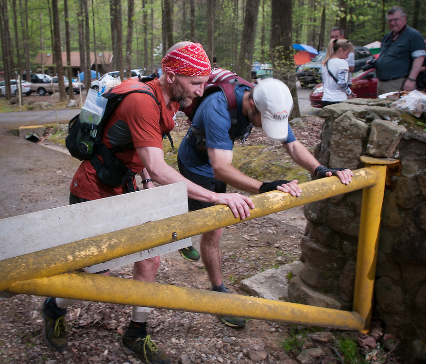 Tim Englund, left, and John Fegyveresi, right, touch the gate to end a loop during the Barkley Marathons.