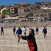 'Attitude at Altitude' Football in Potosi, Bolivia'..Girls play football during the Liga Deportiva San Cristobal finals matches on the stone and gravel surface high in the hills over Potosi. Potosi, Bolivia 9th May 2010........'Attitude at Altitude' Football in Potosi, Bolivia'..The Calvario players greet the final whistle with joyous celebration, high fives and bear hugs the players are sprayed with local Potosina beer after a monumental 3-1 victory over arch rivals Galpes S.C. in the Liga Deportiva San Cristobal. The Cup Final, high in the hills over Potosi. Bolivia, is a scene familiar to many small local football leagues around the world, only this time the game isn't played on grass but a rock hard earth pitch amongst gravel and boulders and white lines that are as straight as a witches nose, The hard surface resembles the earth from Cerro Rico the huge mountain that overlooks the town. .. Sitting at 4,090M (13,420 Feet) above sea level the small mining community of Potosi, Bolivia is one of the highest cities in the world by elevation and sits 'sky high' in the hills of the land locked nation. ..Overlooking the city is the infamous mountain, Cerro Rico (rich mountain), a mountain conceived to be made of silver ore. It was the major supplier of silver for the spanish empire and has been mined since 1546, according to records 45,000 tons of pure silver were mined from Cerro Rico between 1556 and 1783, 9000 tons of which went to the Spanish Monarchy. The mountain produced fabulous wealth and became one of the largest and wealthiest cities in Latin America. The Extraordinary riches of Potosi were featured in Maguel de Cervantes famous novel 'Don Quixote'. One theory holds that the mint mark of Potosi, the letters PTSI superimposed on one another is the origin of the dollar sign...Today mainly zinc, lead, tin and small quantities of silver are extracted from the mine by over 100 co operatives and private mining companies who still mine the mountain in poor working