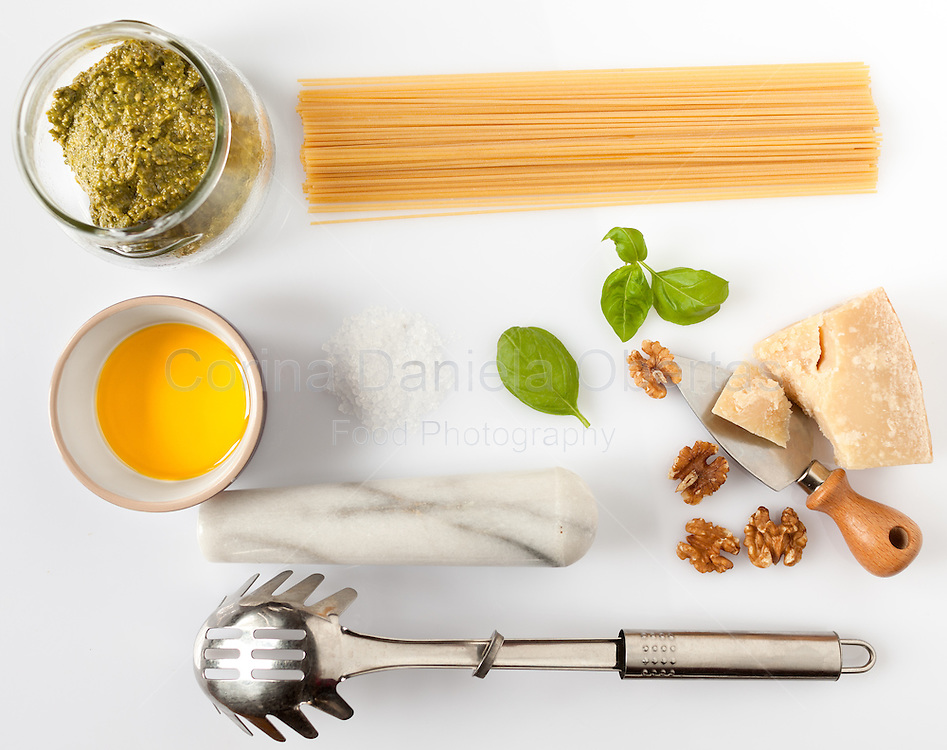 Composition of ingredients and kitchen utensils for spaghetti with pesto.