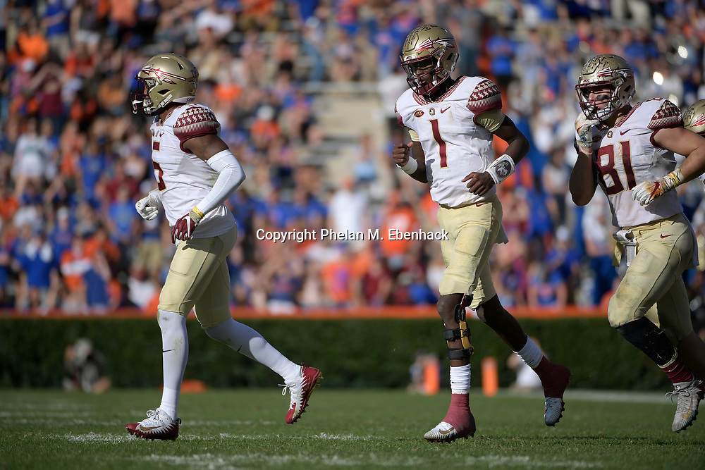 Florida State wide receiver Ermon Lane (5), quarterback James Blackman (1) and tight end Ryan Izzo (81) run onto the field during the second half of an NCAA college football game against Florida Saturday, Nov. 25, 2017, in Gainesville, Fla. FSU won 38-22. (Photo by Phelan M. Ebenhack)