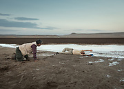 Botanist and lepidopterologist getting water sample in a wetland made of saline mud. The wetter area is very soft, so they must roll on the ground so they don't sink in quicksand.