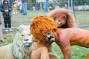 Man and woman in lion and lioness costumes and bodypaint in a cage