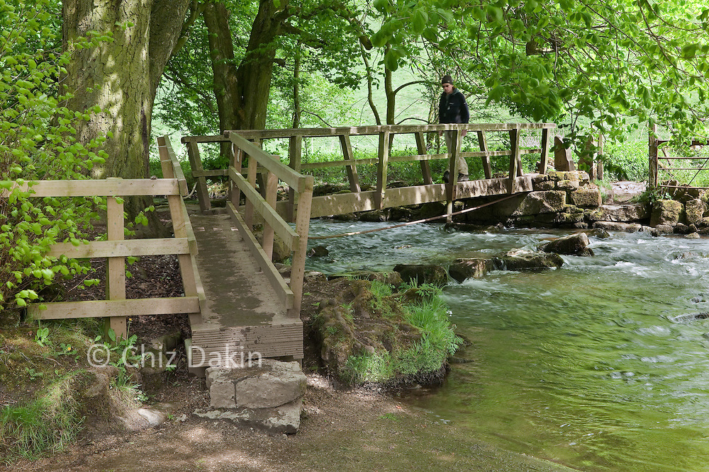 Walker on the footpath bridge crossing the R. Dove which marks the boundary between Beresford Dale and Wolfscote Dale, Peak District National Park