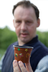 Man with flower decorated pot on community Allotment open day,