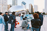 Tourist look on as an artist paints the Cload Gate in Millennium Park in Chicago, Illinois.