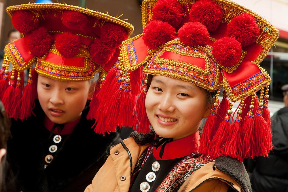 Two girls in traditional headdress on Mott Street before the start of the parade.