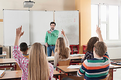 Teacher pointing to students with arms raised, Bavaria, Germany