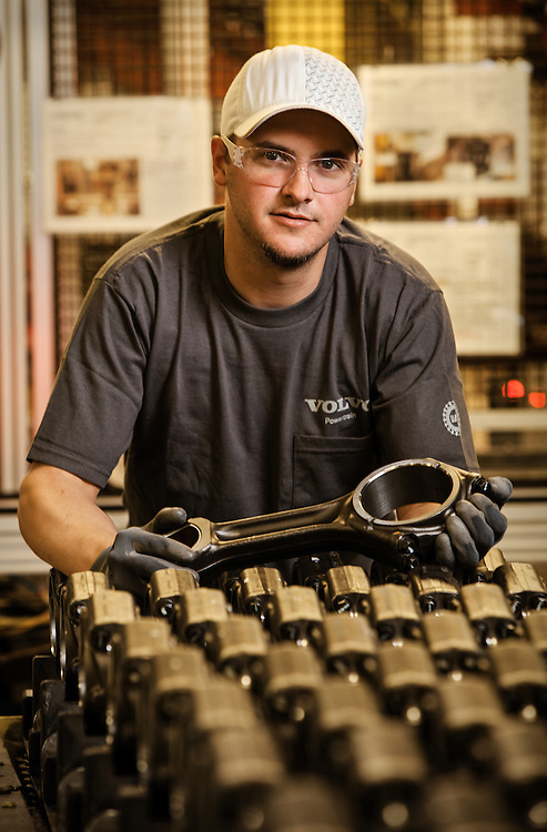 Volvo Technician holding a connecting rod for a diesel engine