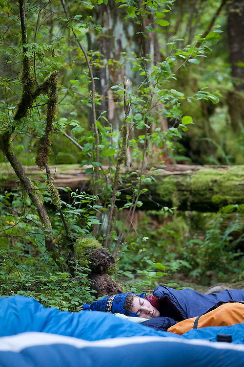 Zach Podell-Eberhardt sleeps on the ground in his sleeping bag at Seven and a Half Mile Camp, on the Eagle Creek Trail, Columbia River Gorge National Scenic Area, Oregon.