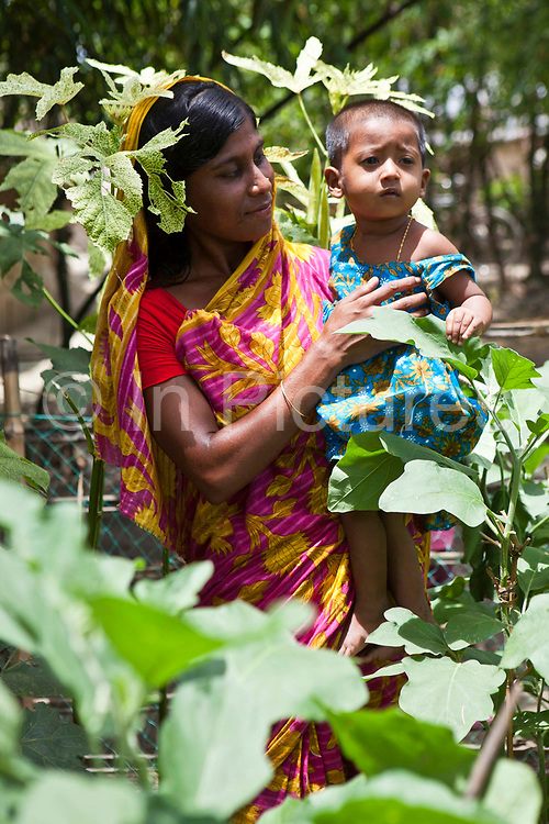 Aklima Katum with her daughter Mahmuda, who is 1.5 years old.  They are growing vegetables for themselves and also local neighbours. The vegetables being grown are Kankon; leafy vegetables, aubergine, okra, and banana.  The women have received nutrition training from IFB.<br /> Impact Foundation Bangladesh (IFB) provides care, support and treatment to people with disabilities in Bangladesh.