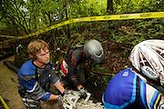 Brad ? and Bill Dragoo (silver helmet) push R1200GS out of deep, wet creek while Briana Thompson rides bike.