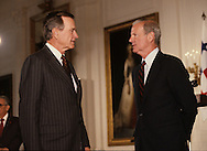 James Baker III talking to President H W Bush (Bush 41) in the East Room of the White House  in May 1990.  ..Photograph by Dennis Brack bb25