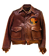 """This type A-2 flight jacket belonged to Leonard J. Otten, a pilot attached to the 571st Squadron of the 390th Bomb Group. On the front of the jacket is the 571st Squadron insignia patch, a wolf in uniform gripping a bomb. Above the patch is a name plate reading """"L.J. Otten"""". There is no artwork on the back to identify to the aircraft Otten flew, or the amount of missions Otten participated in."""
