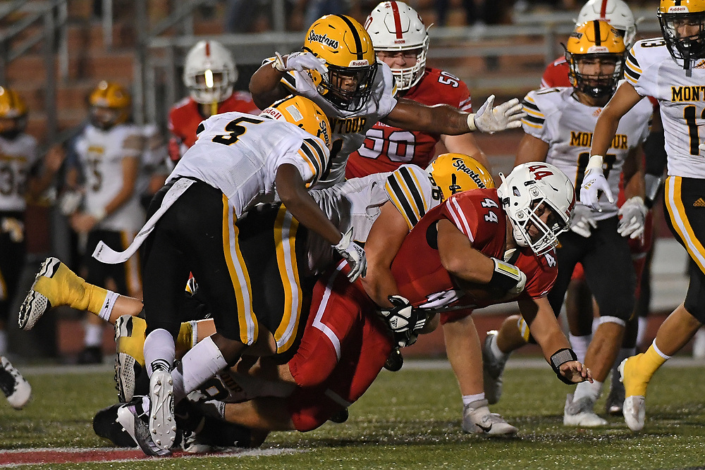 Dylan Sleva #44 of the Moon Tigers is wrapped up for tackle by James Halaja #66 and Keino Fitzpatrick II #5 of the Montour Spartans in the second half during the game at Tiger Stadium on September 3, 2021 in Moon Township, Pennsylvania.