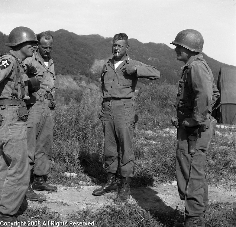 An officer with the Second Infantry Division, U.S. Army talks with other officers during the Korean War. These are photos of the 2nd Infantry Division in the Korean War in 1950 or 1951.