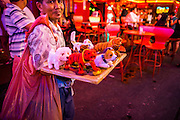 "12 JANUARY 2013 - BANGKOK, THAILAND:  A souvenir vendor walks through the red light district of Soi Cowboy trying to sell knick-knacks to tourists. Prostitution in Thailand is illegal, although in practice it is tolerated and partly regulated. Prostitution is practiced openly throughout the country. The number of prostitutes is difficult to determine, estimates vary widely. Since the Vietnam War, Thailand has gained international notoriety among travelers from many countries as a sex tourism destination. One estimate published in 2003 placed the trade at US$ 4.3 billion per year or about three percent of the Thai economy. It has been suggested that at least 10% of tourist dollars may be spent on the sex trade. According to a 2001 report by the World Health Organisation: ""There are between 150,000 and 200,000 sex workers (in Thailand).""    PHOTO BY JACK KURTZ"