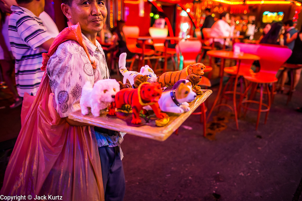 """12 JANUARY 2013 - BANGKOK, THAILAND:  A souvenir vendor walks through the red light district of Soi Cowboy trying to sell knick-knacks to tourists. Prostitution in Thailand is illegal, although in practice it is tolerated and partly regulated. Prostitution is practiced openly throughout the country. The number of prostitutes is difficult to determine, estimates vary widely. Since the Vietnam War, Thailand has gained international notoriety among travelers from many countries as a sex tourism destination. One estimate published in 2003 placed the trade at US$ 4.3 billion per year or about three percent of the Thai economy. It has been suggested that at least 10% of tourist dollars may be spent on the sex trade. According to a 2001 report by the World Health Organisation: """"There are between 150,000 and 200,000 sex workers (in Thailand).""""    PHOTO BY JACK KURTZ"""