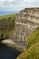 Hikers look like ants atop the bluffs at the Cliffs of Moher