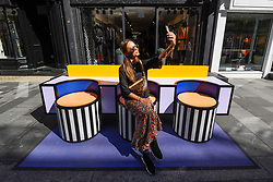 "© Licensed to London News Pictures. 14/09/2019. LONDON, UK.  A tourist takes a selfie on a sculptural bench as ""Walala Lounge"" opens in Mayfair's South Molton Street.  Artist and designer Camille Walala's installation comprises 10 sculptural benches, accompanied by planters and a series of oversized flags strung, bunting-style, from shopfront to shopfront, converting the street into an immersive corridor of colour as part of this year's London Design Festival.  Photo credit: Stephen Chung/LNP"